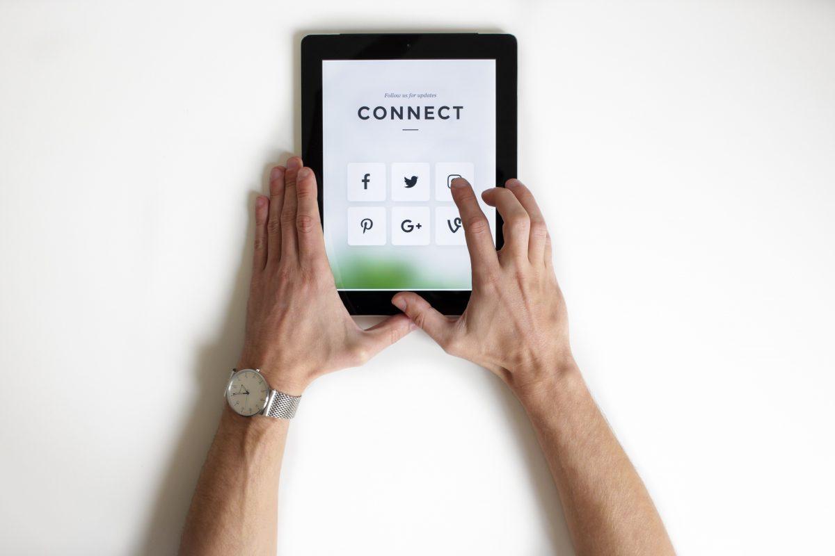 Imagem destacada do post da Dotin Digital referente a empresa marcar presença nas redes sociais, onde uma pessoa segura um tablet com vários ícones de redes sociais.