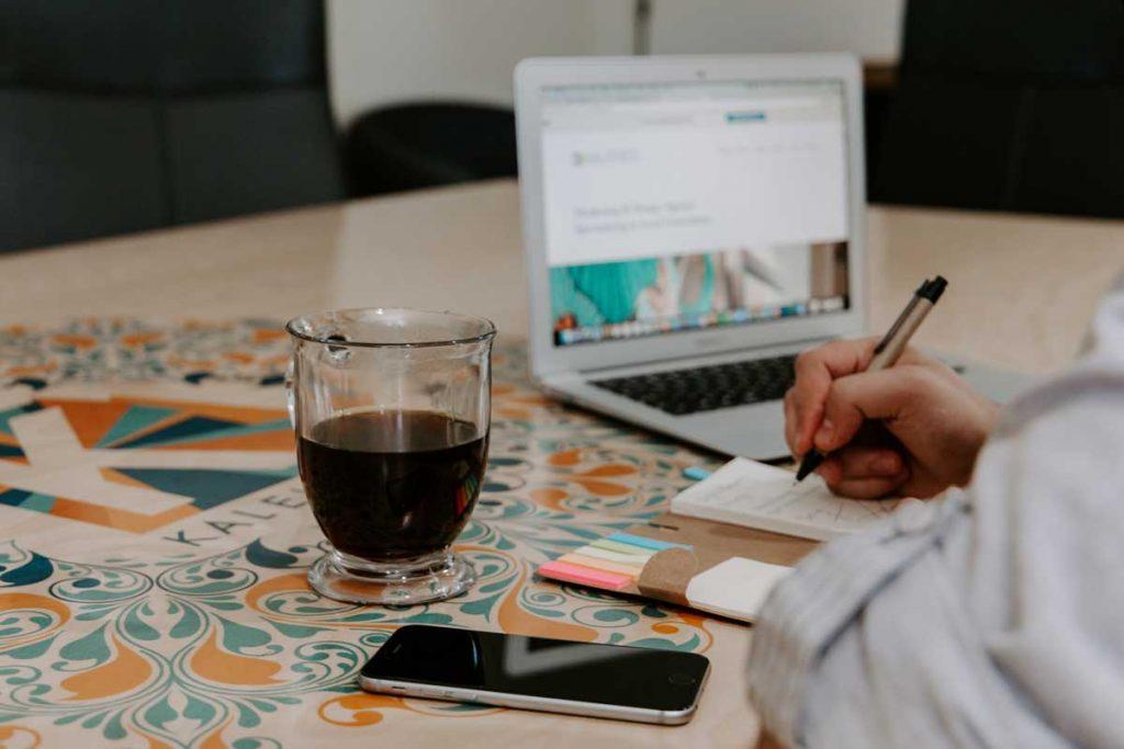 Pessoa fazendo anotações em um caderno, com uma xícara de café, smartphone e notebook em sua mesa.