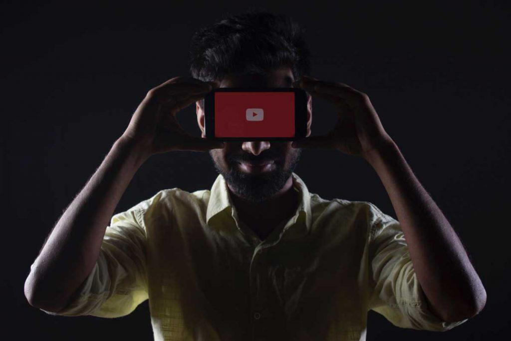 Homem segurando um smartphone com a página de splash do youtube. Produção de visual é uma tendência de marketing digital.