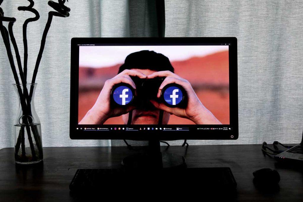 Tela de computador exibindo uma pessoa com um binóculo olhando o logo do facebook.