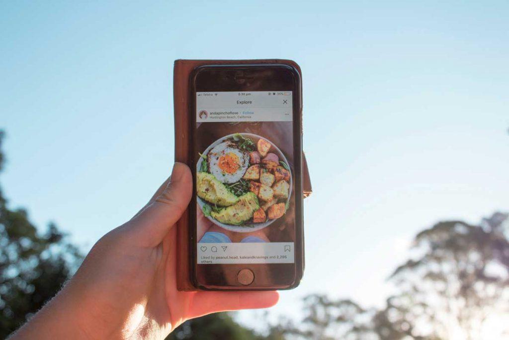 Pessoa segurando um smartphone com uma postagem do instagram de um prato de comida.