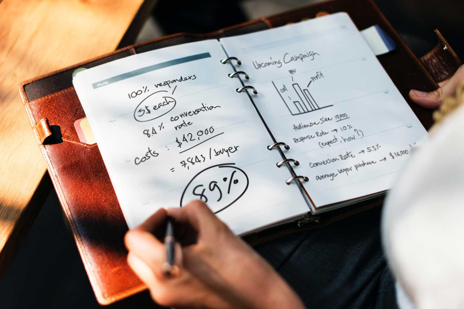 Cadernos com anotações com métricas para investir em marketing digital.