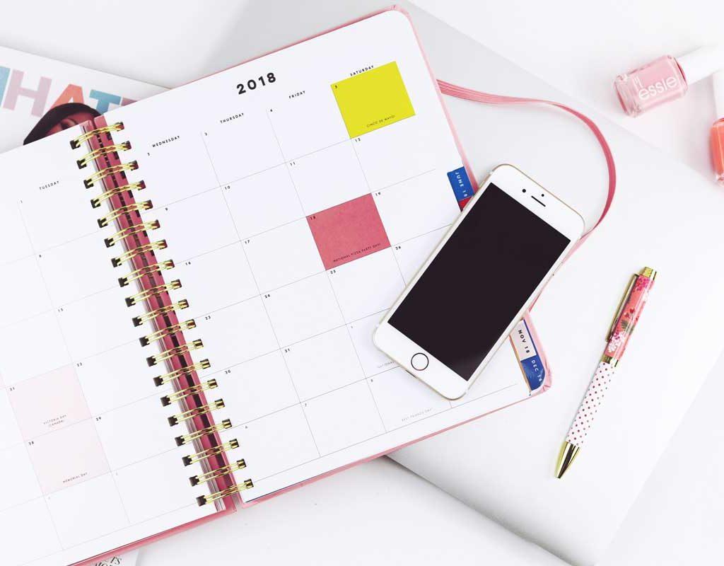 Imagem com uma calendário aberto em cima de uma mesa próximo a um smartphone