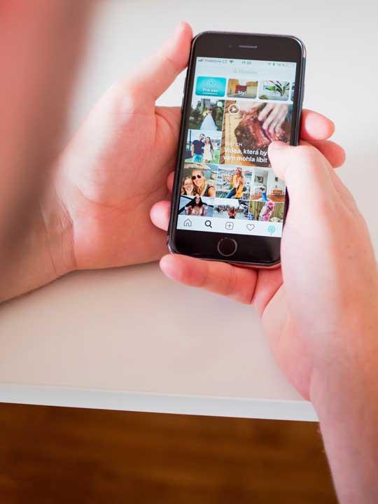 Pessoa segurando um celular exibindo um feed do instagram