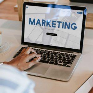 Agência de marketing digital - Pessoa utilizando um notebook exibindo a palavra marketing ilustrando uma