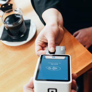 Imagem de uma pessoa pagando seu café em uma maquina de cartão de crédito.