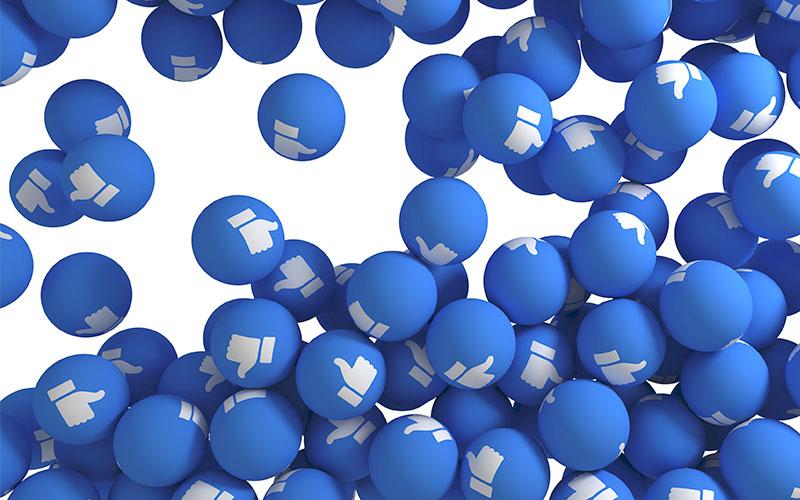 Pequenas bolas, como as de piscina de bolinha, azuis com o like no Facebook desenhado.