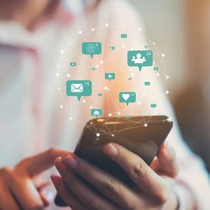 Imagem de uma pessoa utilizando o celular com várias informações salyando da tela, ilustrando estratégias de marketing digital