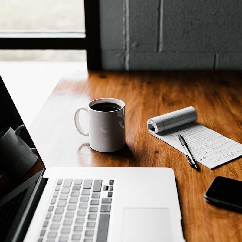 Imagem de uma mesa com laptop e caderneta, ilustrando home office