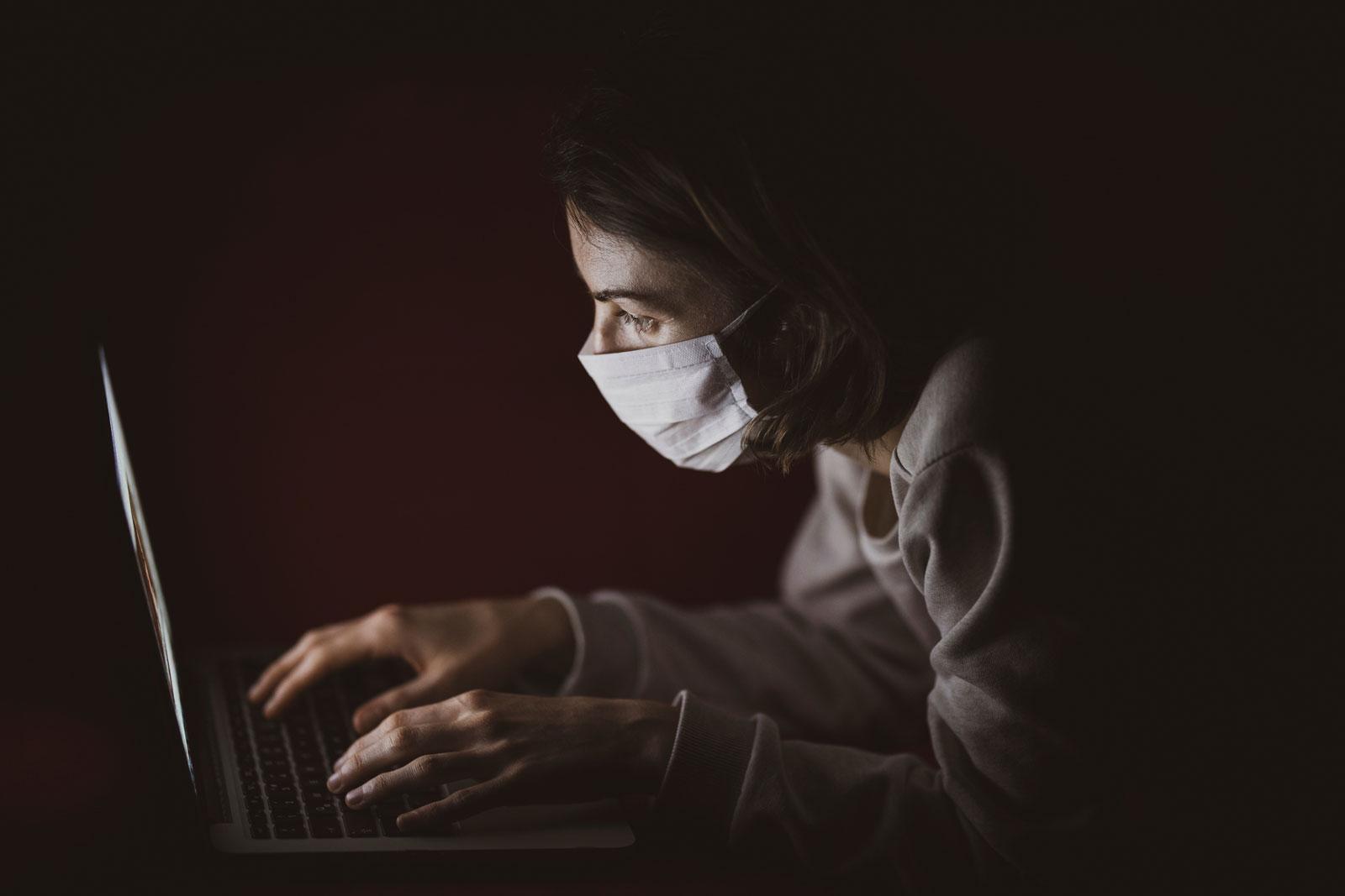 pessoa acessando o computador utilizando máscara buscando inovação durante a pandemia de coronavírus